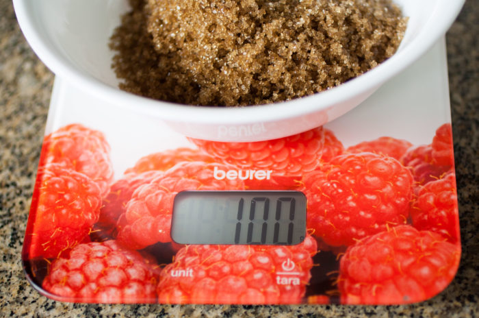 Kitchen scale with a white bowl with brown sugar on top.