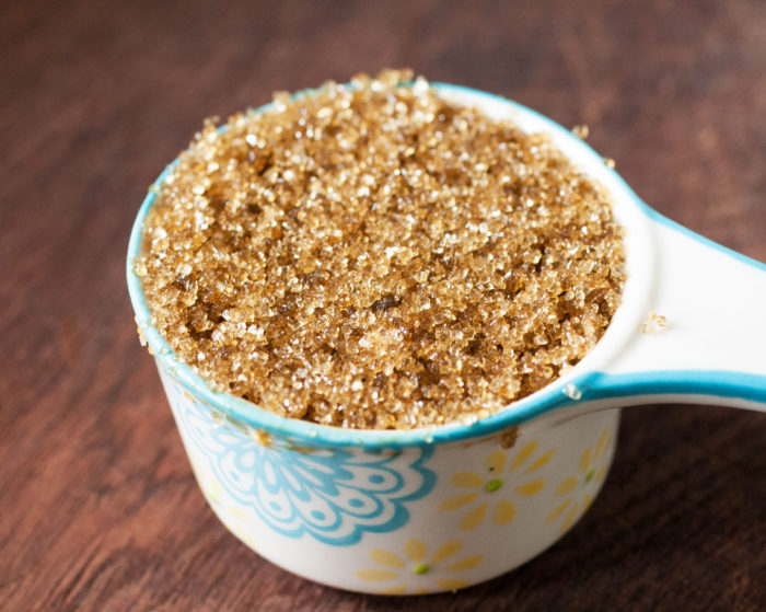 Brown sugar in a white and light blue measuring cup.