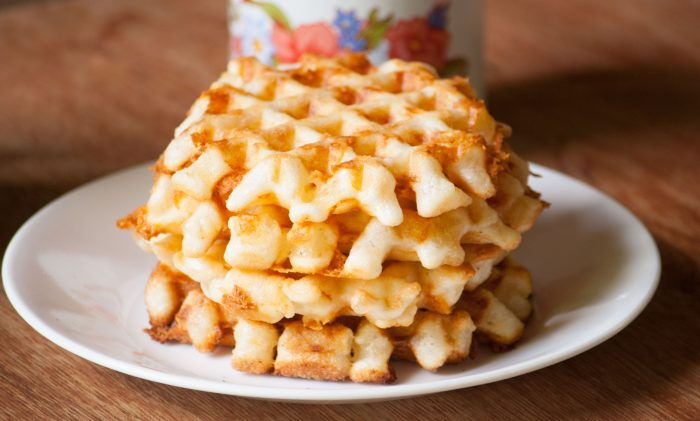 4 cheese waffles stuck on top of each other on a white plate