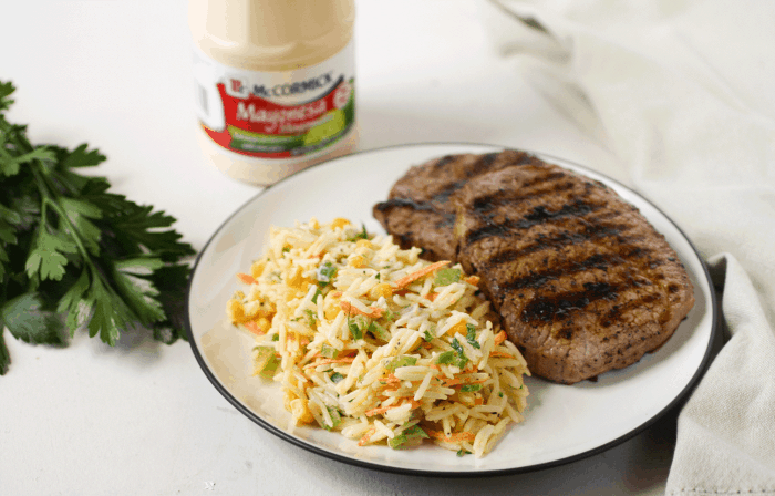 Plate with rice salad and steak. Behind, a jar of mayo