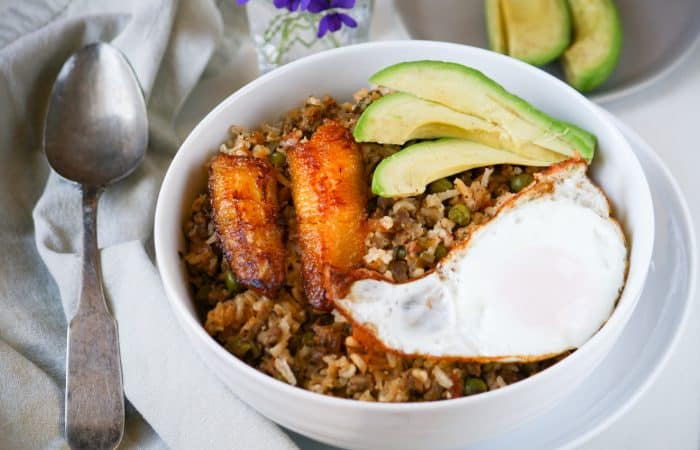 fried rice in a bowl with plantain, fried egg, and avocado
