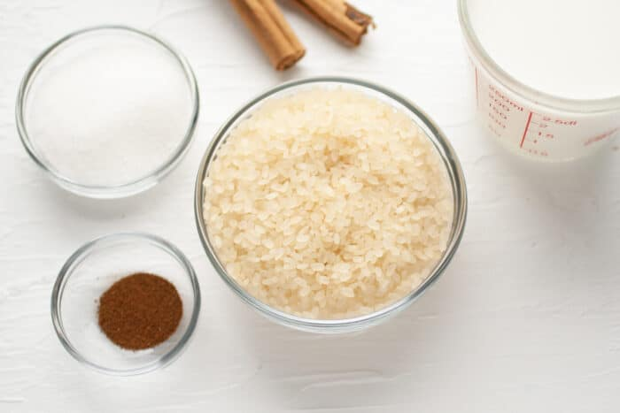 ingredients for bolivian rice pudding: rice, cinnamon, cloves, sugar and milk