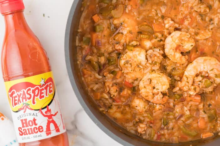 pot with stew and hot sauce on the side