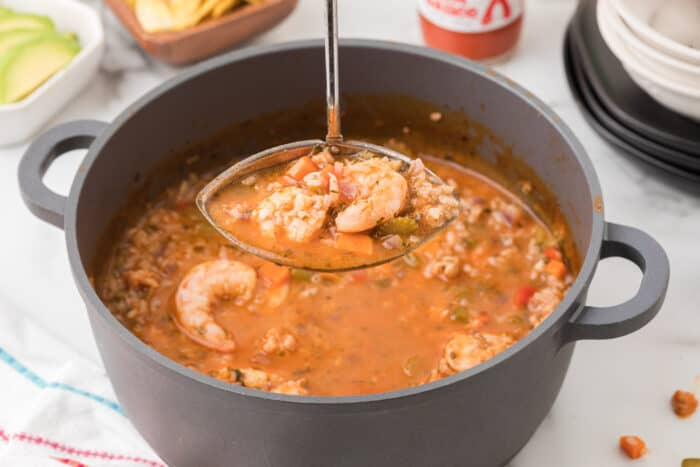 pot with soup, ladle with rice and shrimp